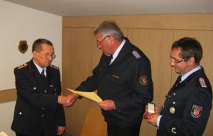 Stadtbrandmeister Wolfgang Schulz überreicht Friedrich Wasmuß sen. das Abzeichen des Niedersächsischen Landesfeuerwehrverbandes für 60 jährige Mitgliedschaft